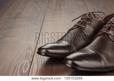 brown leather shoes on the wooden background