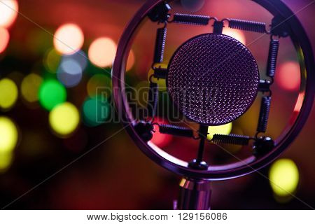 Closeup photo of condenser microphone in colorful bokeh