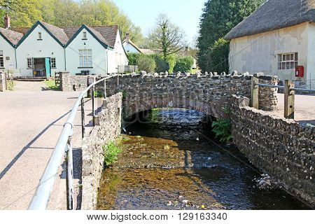 A quaint picture postcard Devon Village with thatched cottages and a small stream running through there is a local event taking place in the Village hall through the doors of the building on the left