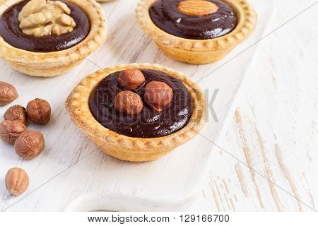 Nutty chocolate dessert small tarts closeup on a white background