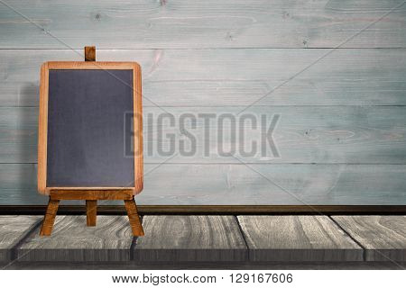 Image of a blackboard against wooden table in front of wooden wall