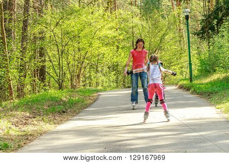 young girl in protective equipment and rollers scating with mother in park, outdoor portrait