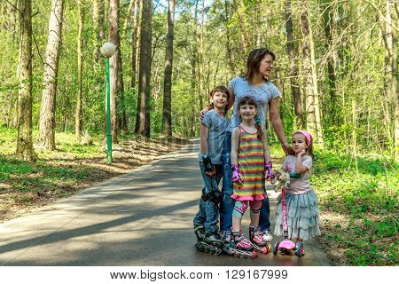 young girls and boy in protective equipment and rollers scating with mother in park, family outdoor portrait