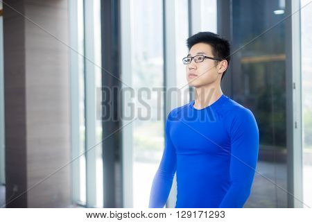 young asian man doing yoga in modern gym