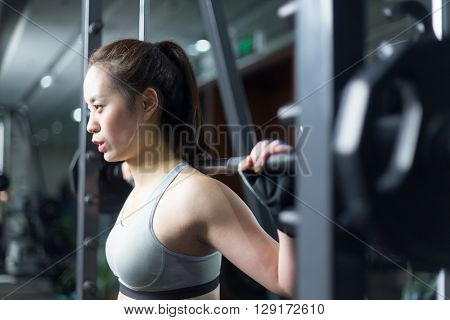 young asian girl working out in modern gym