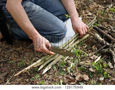 Preparing a campfire for cooking on the nature. The image of a man who sits on his knees in the middle of the forest. A man holds a knife and sharpens the branches of trees.