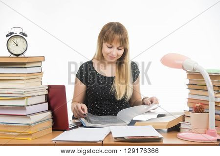 A Student At A Table Littered With Books In The Library With A Smile, Turning The Pages In A Folder