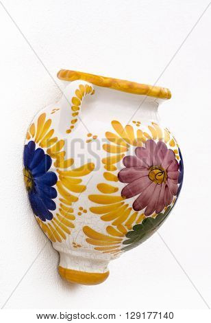 mediterranean souvenirs single painted decorative wall pot. Shot in shallow depth of field in the colors of yellowblue green and purple on a white wall background with room for text and copy space ideal for a poster or a holiday event