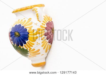 souvenirs from the mediterranean of a single painted decorative wall pot. Shot in shallow depth of field in the colors of yellowblue green and purple on a white wall background with room for text and copy space ideal for a poster menu or a holiday event