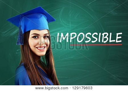 Young graduated woman near blackboard with word impossible transformed into possible