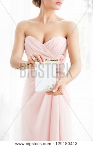 Wedding polygraphy. Invitation in the hands of women. White sheet of paper with a flower pattern.