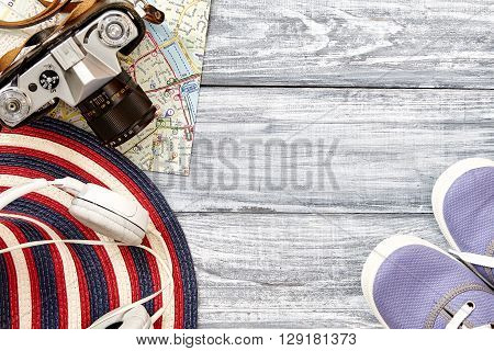 Vacation and travel items. Travel concept - headphones camera shoes map hat on wooden background