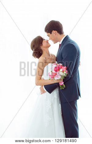 Wedding couple in love. Beautiful bride in white dress with brides bouquet and handsome groom in blue suit standing and embracing each other indoors at home, white bright isolated background