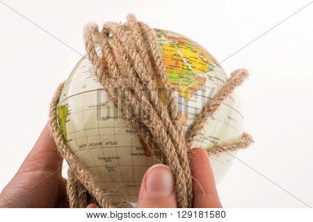 hands holding the globe wrapped in rope