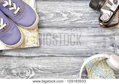 Vacation and travel items. Travel concept - headphones camera shoes map bag on a wooden background