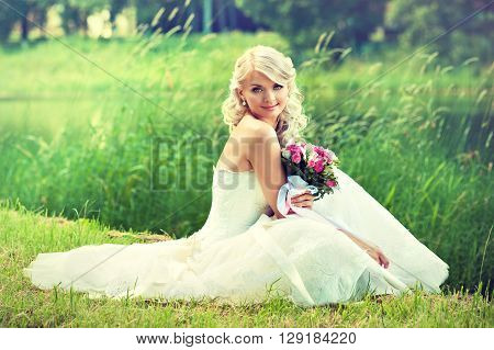 Beautiful blonde bride with a bouquet of flowers  .  