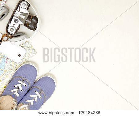 Vacation and travel items. Travel concept - headphones camera shoes map hat telephone on a wooden background