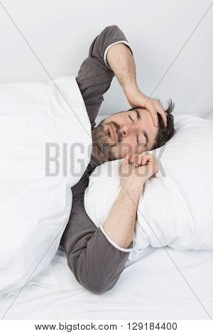 man with beard lying in a bed with white bedding