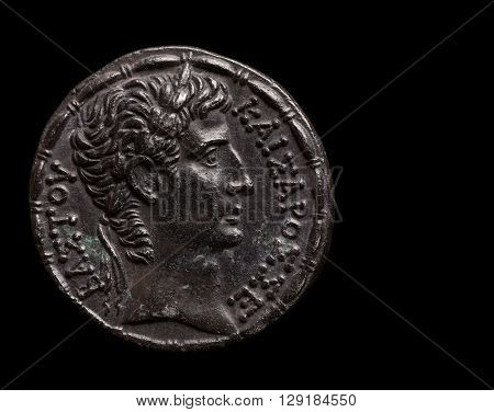 Silver ancient coin of emperor Augustus copy space macro shot isolated on black
