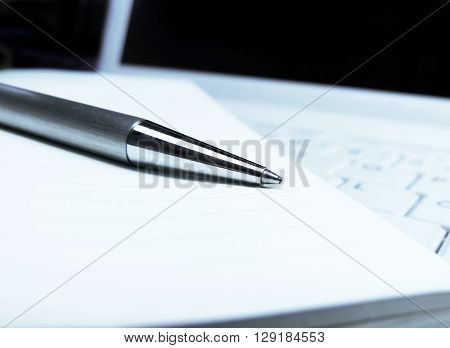 Pen, paper and white laptop. Business concepts.