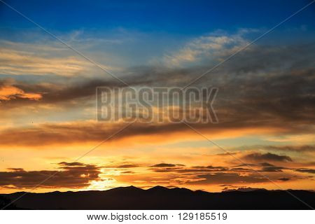 Sun behind dark mountain silhouettes, with colorful sky and clouds