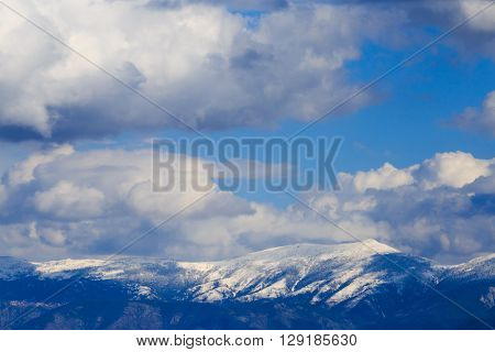 Snowy mountain range with blue sky and clouds.