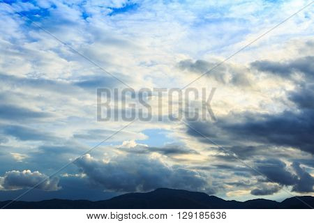 Mountain range with blue sky and heavy clouds.