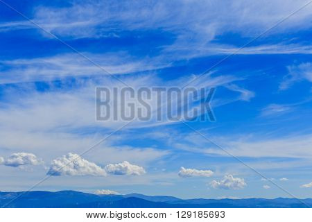 Mountain range with blue sky and clouds.