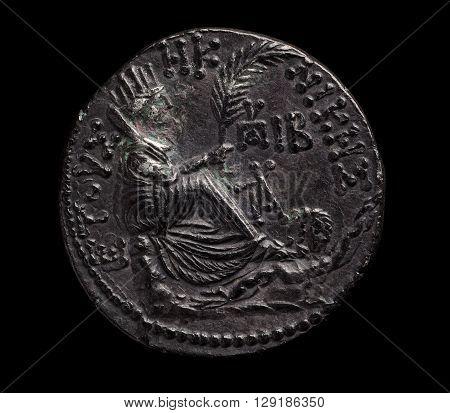 Ancient silver coin in black patina closeup macro shot top view