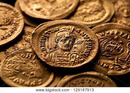 Ancient golden Byzantine coins with emperor portraits macro shot selective focus