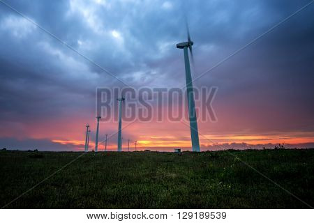 Wind turbines generating electricity against sunrise - copy space