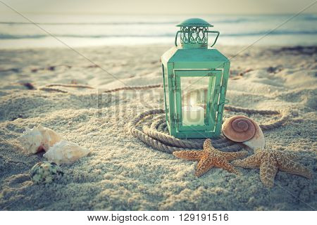 Cross-processed lantern on the beach with shells and rope at sunrise
