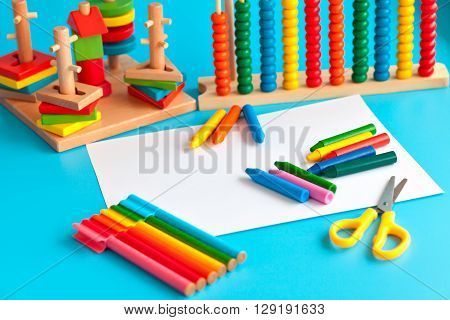 The concept of the artistic activity of the child. Album for drawing and colored pencils on a blue background. toys for learning skills. school supplies.