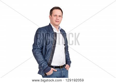 Handsome European Man In White Shirt, Blue Jeans And Blue Leather Jacket. Holding Hands In Pockets W