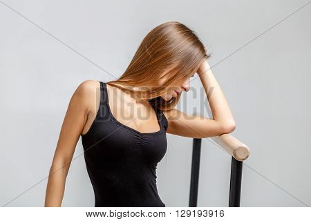 Ballerina in black outfit over light grey studio background
