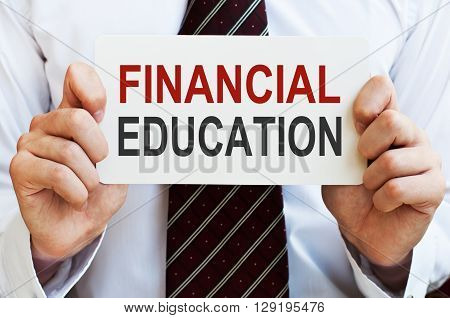 Financial Education. Businessman holding a card with a message text written on it