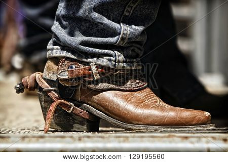 Close up of a rodeo cowboy's boot and spur as he prepares behind the chutes for an upcoming ride.