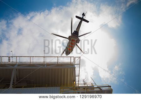 Helicopter landing at oil and gas platform to receive passenger and sent to onshore
