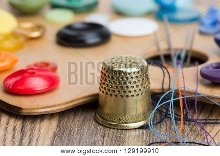 Buttons, Thimble, Needle And Thread On The Palette