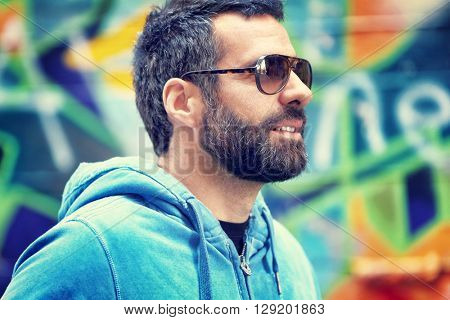 Closeup portrait of a handsome man with stylish beard and sunglasses, standing over colorful city wall background, fashion street look, urban lifestyle