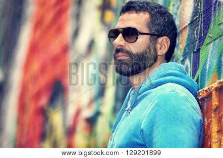Portrait of a handsome man with stylish beard and sunglasses, standing over colorful city wall background, fashion street look, urban lifestyle