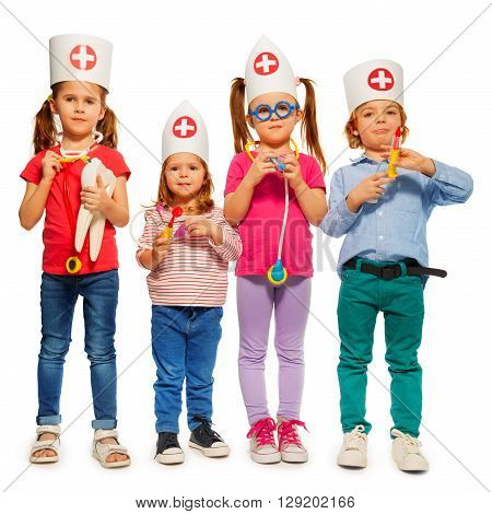 Group of four little kids with medical caps and toy doctor tools, isolated on white