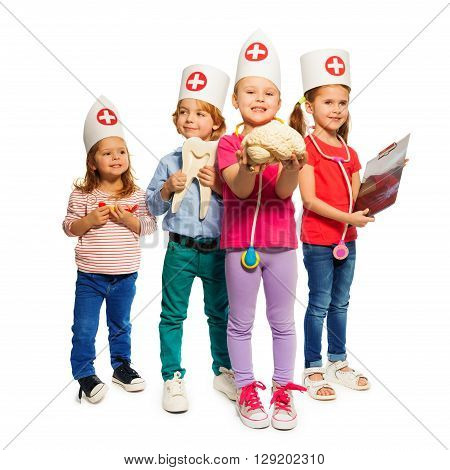 Four little kids playing doctor with toy medical instruments, holding tooth and cerebrum models and x-ray, isolated on white