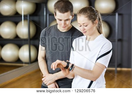 Male And Female Friends Looking At Pedometer