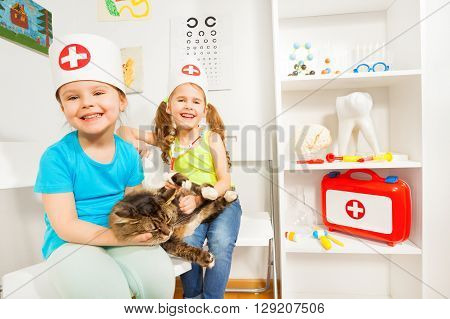 Little girls playing a doctor veterinarian with a cat at medical room.