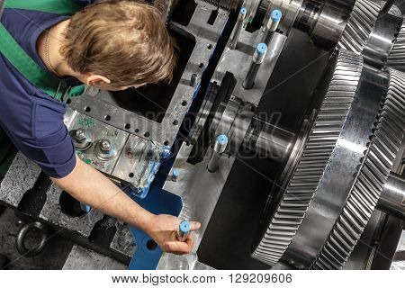 Working man with a small steam turbine. Metal gears. Gear wheels of the engine.