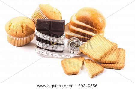 High-calorie products: chocolate cookies biscuits. The chocolate bar is twisted with a centimetric tape. White background.