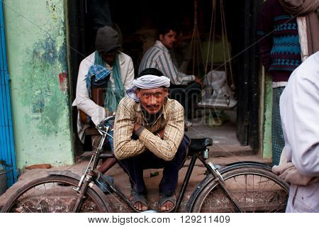 VARANASI, INDIA - JANUARY 1, 2013: Worker in a turban rests leaning on his retro bicycle on the street of the oldest asian city on January 1, 2013. Varanasi urban agglomeration had a population of 1435113