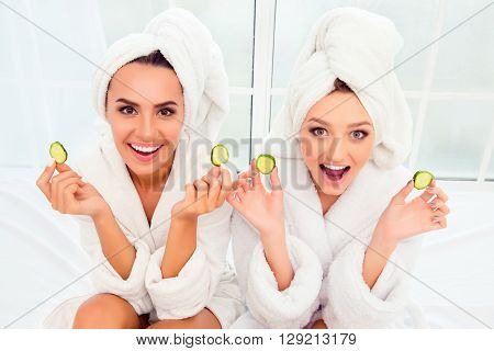 Cheerful Smiling Woman In Bathrobes And Towelson Their Heads Holding Slices Of Cucumber