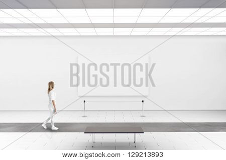 Modern gallery wall mockup. Woman walk in museum hall with blank picture on wall. White clear stand mock up show. Display artwork presentation. Art design empty floor. Expo studio wall in center.